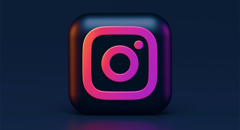 glowing Instagram logo set against a black background